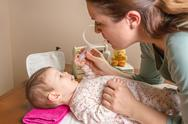 Stock Photo of mother cleaning mucus of baby with nasal aspirator