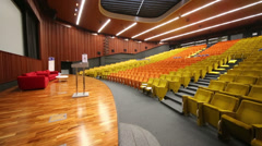 Stage with sofas in modern auditorium with many rows of seats Stock Footage