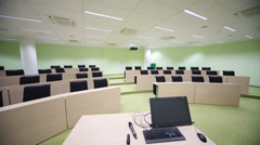 Teacher computer in small modern auditorium with desks Stock Footage