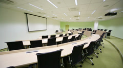 Empty modern auditorium with desks, chairs and light green walls - stock footage