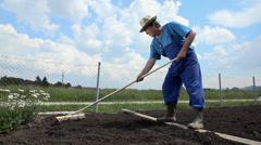 Man using long wooden rake to loosen soil Stock Footage
