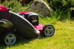 gardening. mowing green lawn with red lawnmower - stock photo