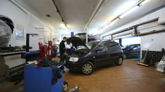Worker, cars and lift in workshop of Service station Avtounivers Stock Footage
