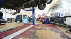 Under car on lift in workshop of small modern service station Stock Footage