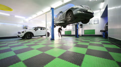 Worker near lifted car in workshop of modern service station Stock Footage