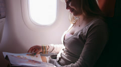 2of2 People, traveler, happy woman traveling on plane, reading magazine - stock footage