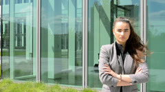 Business women has serious expression and stands before business building - stock footage