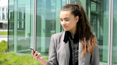 Business woman looks at the mobile before bussines building Stock Footage