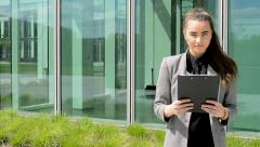 Business woman look to clipboard(paper) then smiles before business building Stock Footage