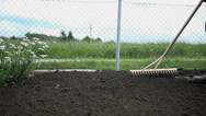 Stock Video Footage of Loa angle shot of farmer using the rake shot in slow motion
