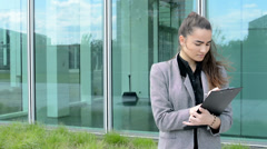 Business woman writes to clipboard(paper) before business building Stock Footage