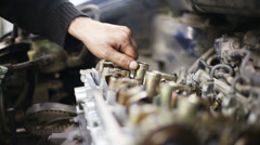 Hand of mechanic unscrews bolt of gasoline car engine Stock Footage