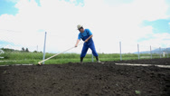 Stock Video Footage of Farmer with hay hat using the rake on his garden