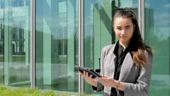 Business woman looks at tablet and then smiles before business building Stock Footage