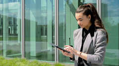 Business woman works on tablet before business building  Stock Footage