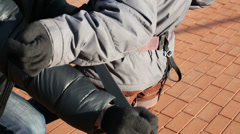 Hands helping child to wear safety equipment for climbing - stock footage