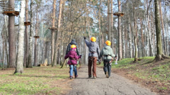 Man with three children in helmets and climbing equipment walk Stock Footage