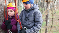 Boy and girl  in helmets and climbing equipment talk outdoor Stock Footage
