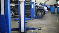 Cars wait repairing and blue lifts at modern Service station Stock Footage