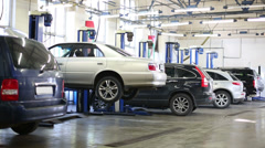 Cars stand in modern service station and car is downing at lift Stock Footage
