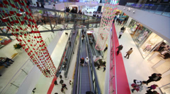 Many buyers move at escalators in modern shopping mall Stock Footage