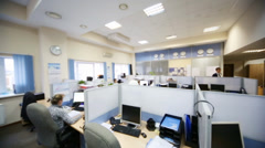 People sit on workplaces with papers separated by partitions Stock Footage