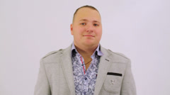Portrait of fat man in shirt and jacket posing at white Stock Footage