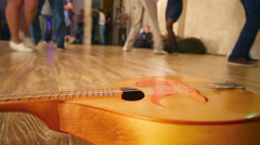 Wooden guitar lies on floor and legs of dancing people move Stock Footage