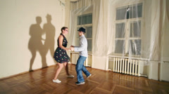 Pretty woman and man in hat dance boogie-woogie near wall Stock Footage