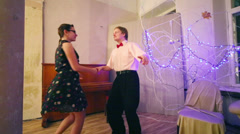 Woman and man in bow-tie dance boogie-woogie near piano in room Stock Footage