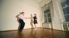 Pretty woman and man in bow-tie dance boogie-woogie near wall Stock Footage