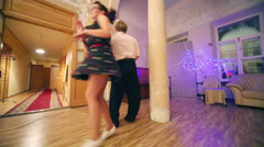 Happy woman and man in bow-tie dance boogie-woogie near column Stock Footage
