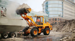 Bulldozer loads wet snow to trucks for snow melting on street Stock Footage