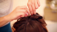 Hands of hairdresser do hairstyle to model using studs Stock Footage