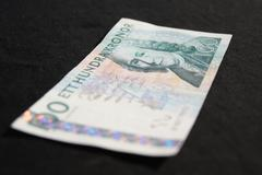 One hundred sek bill with perspective, mostly blurred and sharp person, on bl Stock Photos