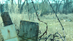 Barbwire fence in Field - stock footage