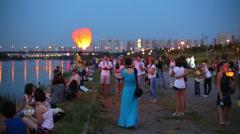 People launch air lantern before running water lanterns Stock Footage