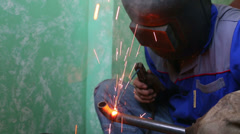 Welder in protective suit and mask welds metal pipes indoor Stock Footage