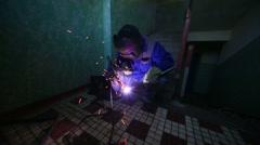 Welder in protective suit and mask welds metal pipes squatting Stock Footage
