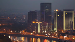 Night panorama of city with illuminated tall buildings and river Stock Footage