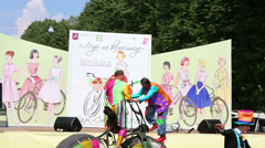 Clowns on big bicycle on day of cycle parade Lady on Bicycle Stock Footage