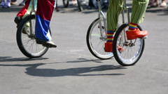 Stock Video Footage of Feet of clowns in colored clothes riding on unicycles outdoor