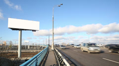 Road with moving cars and large blank billboard at sunny day Stock Footage
