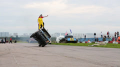 Stunts stand on car riding on two wheels at Festival Stock Footage