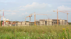 Stock Video Footage of Lots of cranes on construction site in wasteland and green grass