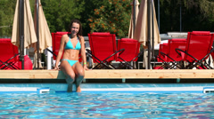 Beautiful girl jumps to pool with pure blue water at summer day Stock Footage