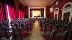Actors rehearse on stage in large hall with rows of spectators Stock Footage