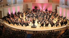 Conductor and musicians play music in Tchaikovsky Concert Hall. - stock footage