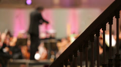 Back of conductor and musicians in concert hall and banister Stock Footage
