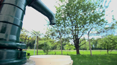 Filling the container with a water from the well pump - stock footage